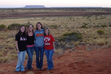 Four travelers standing in the Australian Outback